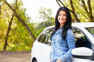 Young happy woman standing by her car with hands in pockets